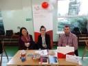 Trzy osoby Przedstawiciele Urzędu Skarbowego w Malborku siedzący na tle baneru biało czerwonego z napisem KAS Krajowa Administracja Skarbowa poniżej Izba Administracji Skarbowej w Gdańsku