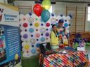 Dwie osoby stojący na tle ściany zrobionej z balonów różnokolorowych. Z lewej strony ścianki stoi baner z napisem Balonowy Twister - Animator zabaw dla dzieci - malowanie twarzy modelowanie balonów mega bańki mydlane zamykanie dzieci w big bańce tatuaże brokatowe kolorowe warkoczyki zabawy z chustą animacyjną gry i zabawy wybuchowa piniata hel do balonów wata cukrowa profesjonalne nagłośnienie fotobudka z akcesoriami.
