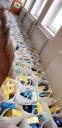 Na podłodze stoi kilkadziesiąt toreb z rożnymi produktami pierwszej potrzeby.